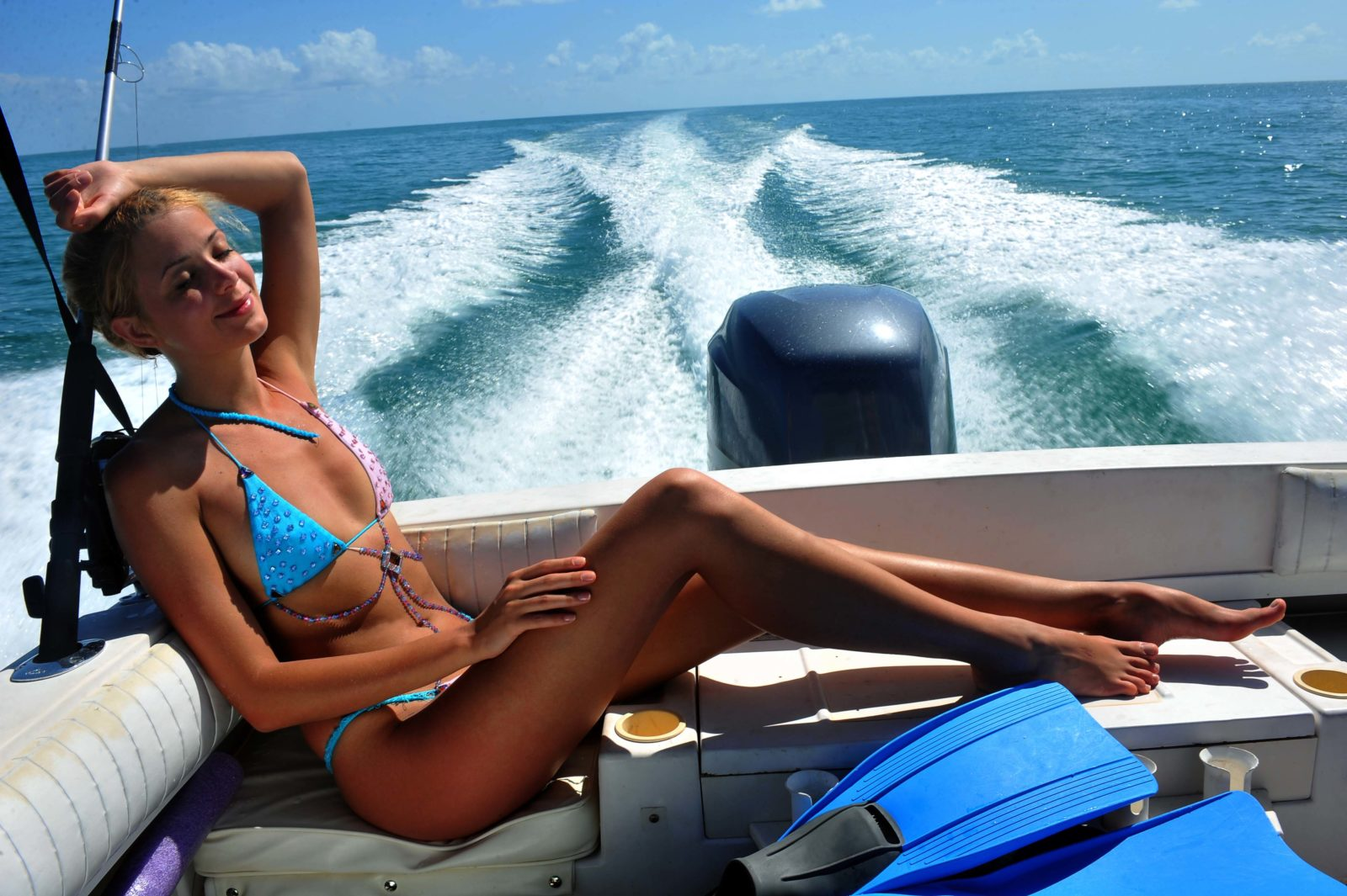 Girl relaxing on the back of motor boat cruizing on speed at tropical water