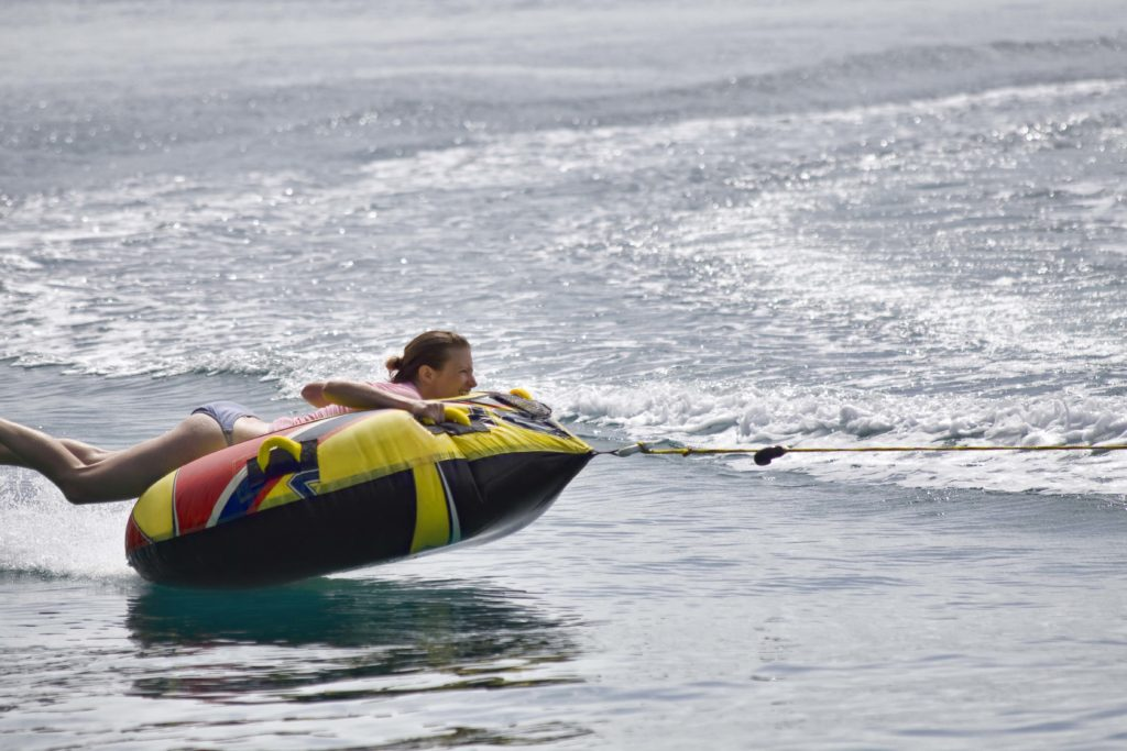 Young woman laying on inner tube being pulled by boat.